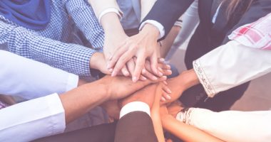 education and awareness | Sickle Cell Disease News | Awareness Campaigns | Many hands placed on top of each other in a huddle